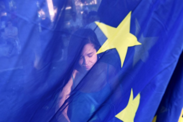 A pro-Euro demonstrator is seen behind a European Union flag during a rally in the northern Greek port city of Thessaloniki, Thursday, July 9, 2015. Hopes that Greece can get a rescue deal that will prevent a catastrophic exit from the euro rose on Thursday, after key creditors said they were open to discussing how to ease the country's debt load, a long-time sticking point in their talks. (AP Photo/Giannis Papanikos)