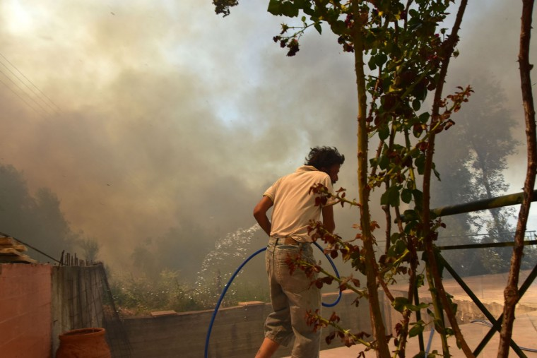 A man tries to extinguish flames as the fire approaches a house at the holiday resort village of Asini, near the town of Nafplio, about 140km (87 miles) southwest of Athens on Monday, July 20, 2015. A 47-year-old policeman was identified as the victim of a fire in a wooded area east of Greek capital on Sunday as firefighters were battling with dozens of fires around Greece the last four days. Foreign forces support Greek firefighters following Prime Minister Alexis Tsipras' request for help. (AP Photo/Vangelis Bougiotis)