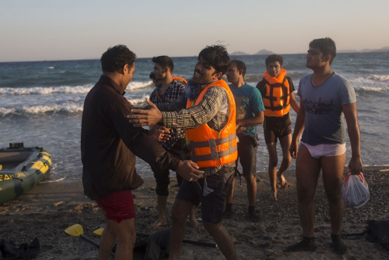 Migrants from Pakistan react as they disembark after rowing a dinghy from the Turkish coasts to the Greek island of Kos, Monday, July 13, 2015. Some tens of thousands of migrants have arrived in Greece so far this year, usually on Aegean islands from the nearby Turkish coast, overwhelming local authorities and aid groups say Greece needs more help from the European Union to deal with the influx. (AP Photo/Santi Palacios)
