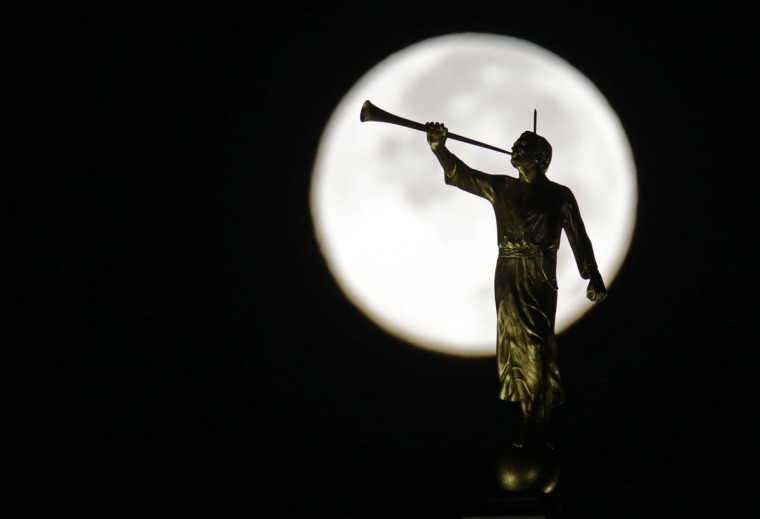 The moon sets behind the gilded statue of the angel Moroni atop the Indianapolis Indiana Temple of The Church of Jesus Christ of Latter-day Saints in Carmel, Ind., Friday, July 31, 2015. (AP Photo/Michael Conroy)