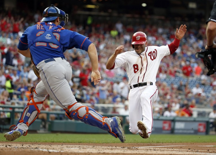 Washington Nationals' Danny Espinosa (8) scores on a single by Yunel Escobar as New York Mets catcher Anthony Recker (20) goes for the throw during the first inning of a baseball game at Nationals Park, Monday, July 20, 2015, in Washington. (AP Photo/Alex Brandon)
