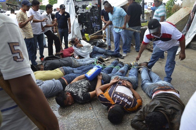 Captured men lie face down and tied up after rival taxi unions fighting for permits clashed in the city of Chilpancingo, Mexico, Monday, July 20, 2015. Several taxi drivers were injured and dozens of vehicles were destroyed. (AP Photo/Alejandrino Gonzalez)