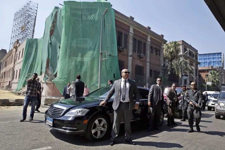 Security guards stand next to the car carrying Italian Foreign Minister Paolo Gentiloni as he visits the site of an explosion at the Italian Consulate in downtown, Cairo, Egypt, Monday, July 13, 2015. Gentiloni's visit comes days after a car bomb ripped into the Italian Consulate in Cairo early Saturday, destroying a section of the historic building in a powerful blast that killed one Egyptian and marked the most significant attack yet on foreign interests as militants target the country's security forces. (AP Photo/Hassan Ammar)