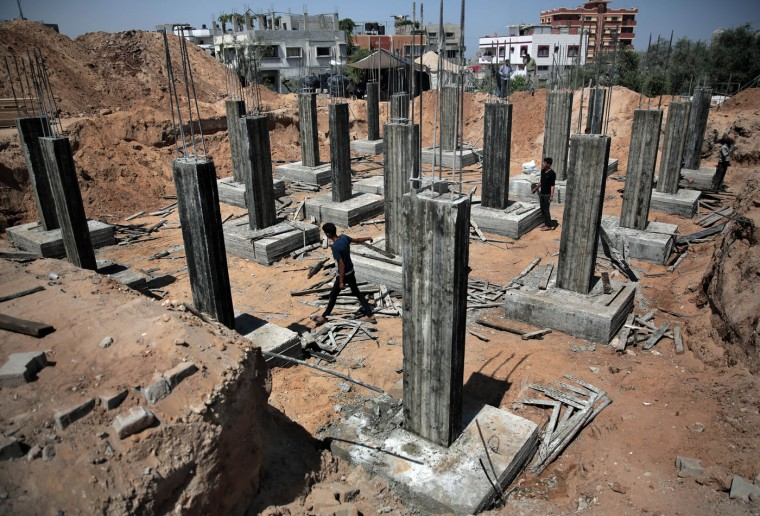 Palestinian workers rebuild a house which was destroyed during the last summer's war between Israel and Hamas, as the long-awaited reconstruction began in Shijaiyah neighborhood eastern Gaza City on Thursday, July 23, 2015. Construction has started on the first homes that will be rebuilt in the Gaza Strip since the devastating war destroyed much of the territory's infrastructure. (AP Photo/Khalil Hamra)