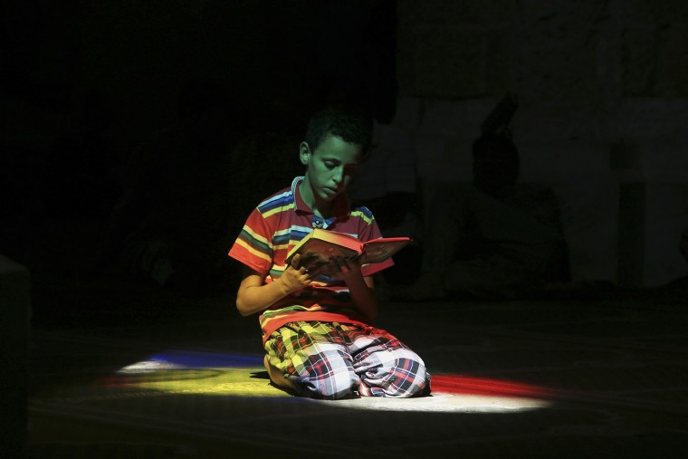 A Palestinian child recites verses from the Quran, Islam's holy book, as he waits for the noon prayer at a mosque during the holy month of Ramadan in Gaza City in the northern Gaza Strip, Thursday, July 9, 2015. Muslims throughout the world are marking the month of Ramadan, the holiest month in the Islamic calendar during which devotees fast from dawn till dusk. (AP Photo/Adel Hana)