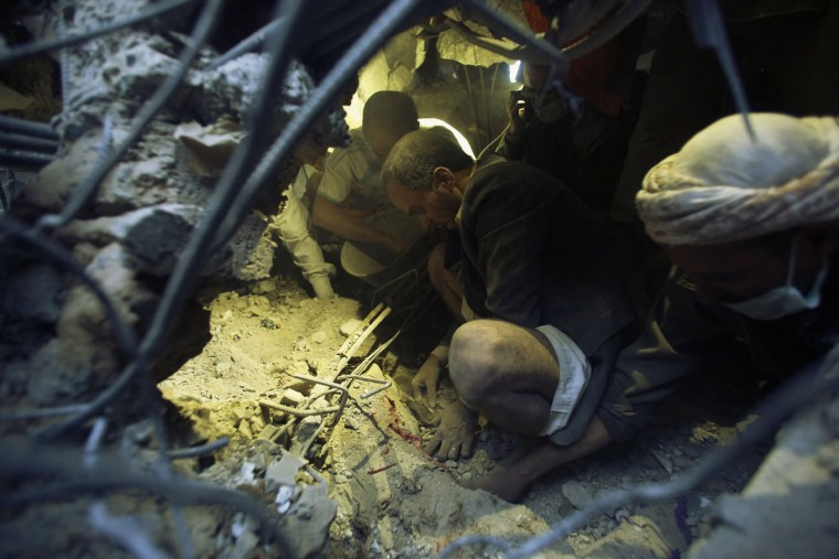 Men uncover the body of a girl under the rubble of a house destroyed by a Saudi-led airstrike in Sanaa, Yemen, Thursday, July 2, 2015. The United Nations on Wednesday declared its highest-level humanitarian emergency in conflict-torn Yemen, where over 80 percent of the population needs assistance. U.N. officials have said the Arab world's most impoverished country is now a step away from famine. (AP Photo/Hani Mohammed)