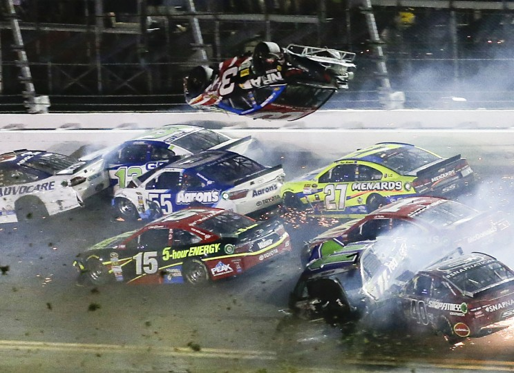 Austin Dillon (3) goes airborne and hits the catch fence as he was involved in a multi-car crash on the final lap of the NASCAR Sprint Cup series auto race at Daytona International Speedway, Monday, July 6, 2015, in Daytona Beach, Fla. (AP Photo/Terry Renna)
