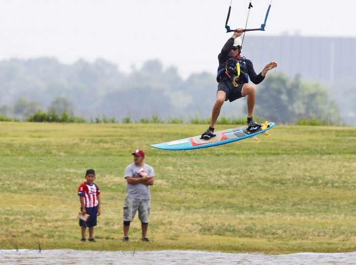 A kiteboarder jumps near the shore at Lake Hefner, Monday, July 6, 2015, in Oklahoma City. (AP Photo/Sue Ogrocki)