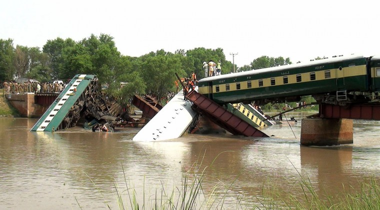 People gather during a rescue operation, after a bridge collapse led a train to fall into a canal in Wazirabad, near Lahore, Pakistan Thursday, July 2, 2015. At least four cars of a train being used to transport Pakistani soldiers fell into a canal because of a bridge collapse in the eastern Punjab province on Thursday, killing at least twelve soldiers, officials said. (AP Photo/Rameez Khan)