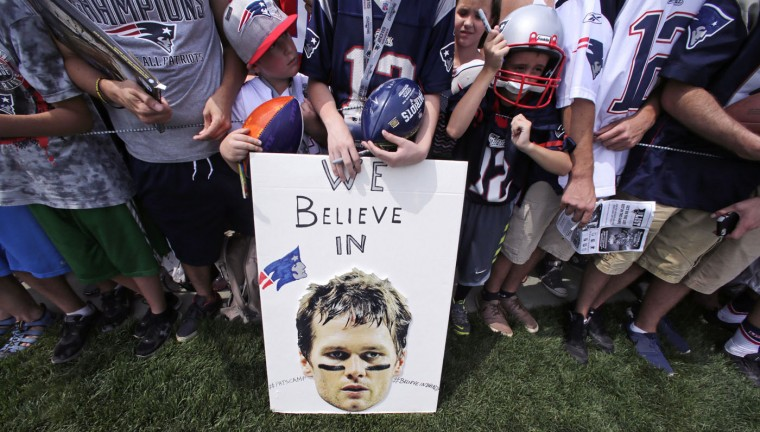 New England Patriots fans wait for practice to complete, while standing behind a sign supporting quarterback Tom Brady, during an NFL football training camp in Foxborough, Mass., Thursday, July 30, 2015. (AP Photo/Charles Krupa)