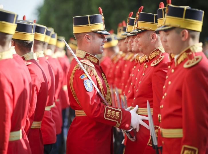 An honor guard soldier adjusts the outfit of a colleague standing in the sunlight before a welcoming ceremony for NATO Secretary General Jens Stoltenberg in Bucharest, Romania, Thursday, July 2, 2015. Stoltenberg is meeting top officials in Romania and will inspect a site where the alliance will build a facility dubbed the NATO Force Integration Unit that is similar to ones planned in Poland, Bulgaria and the three Baltic states — Estonia, Latvia and Lithuania, in reaction to the crisis in Ukraine. (AP Photo/Vadim Ghirda)