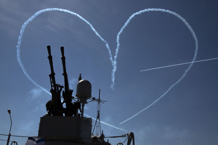 "L-39 jets of the ""Russ"" aerobatic team create by smoke a heart pierced by an arrow during an air show at the International Maritime Defence show in St. Petersburg, Russia, Thursday, July 2, 2015. (AP Photo/Dmitry Lovetsky)"