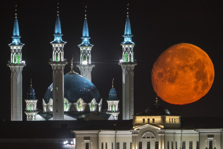 The full moon rises over the illuminated Kazan Kremlin with the Qol Sharif mosque illuminated in Kazan, the capital of Tatarstan, located in Russia's Volga River area about 700 km (450 miles) east of Moscow, early Wednesday, July, 29, 2015. (AP Photo/Denis Tyrin)