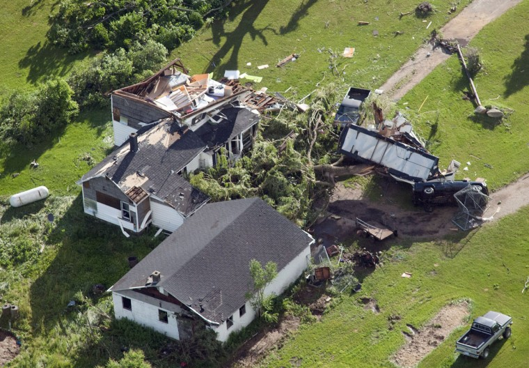 Debris surrounds a damaged house and car in southwest Tuscola County, Mich., Tuesday, June 23, 2015. A series of severe thunderstorms that pushed damaging winds and tornados into several parts of Michigan wrecked homes and knocked out power to thousands of people, officials said Tuesday. (Jeff Schrier/The Saginaw News via AP)