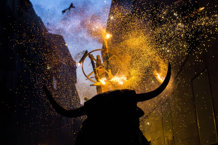 "A flaming fake bull known as a ""Toro de fuego"" runs after revelers during San Fermin festival in Pamplona, Spain, Monday, July 13, 2015. Revelers from around the world arrive in Pamplona every year to take part in some of the eight days of the running of the bulls. (AP Photo/Andres Kudacki)"