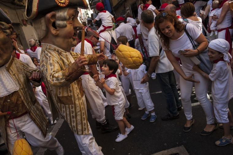 A young boy looks up at a ''Cabezudo'', a member of San Fermin Parade of Giants, at the San Fermin Festival, in Pamplona, Spain, Monday, July 13, 2015. Revelers from around the world arrive to Pamplona every year to take part in some of the eight days of the running of the bulls. (AP Photo/Alvaro Barrientos)