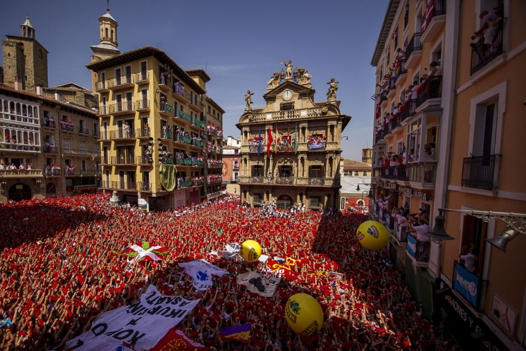 "Revelers hold up traditional red neckties during the launch of the ""Chupinazo"" rocket, to celebrate the official opening of the 2015 San Fermin fiestas in Pamplona, Spain, Monday, July 6, 2015. (AP Photo/Andres Kudacki)"