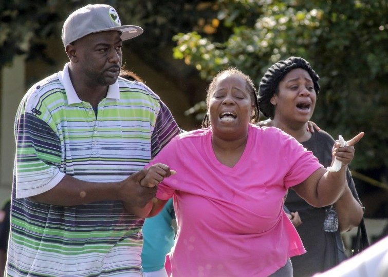 People react near the scene of a shooting, Thursday, July 9, 2015, in the East Lake neighborhood of Atlanta. Police say a 16-year-old girl was shot in the chest and killed in a bedroom of her family's apartment in The Villages of East Lake. (John Spink/Atlanta Journal-Constitution via AP)