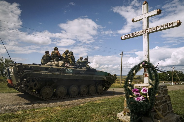 Russia-backed separatist APC rides by an Orthodox cross with a sign reading Save and Guard, with a memorial to the victims of the Malaysian Airlines MH17 plane crash, in the back, near the village of Hrabove, eastern Ukraine, Thursday, July 16, 2015. A year since a Malaysia Airlines Boeing 777 was blown out of the sky over war-ravaged eastern Ukraine, killing 298 people, there has been little official word of progress in determining what brought down Flight MH17. (AP Photo/Mstyslav Chernov)