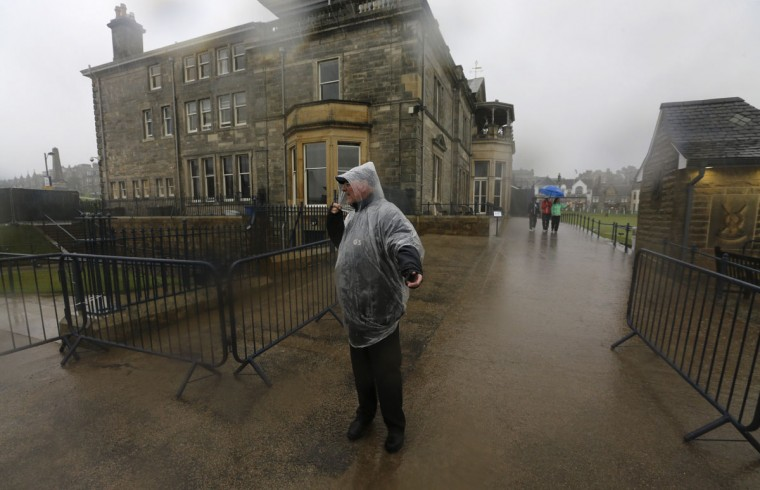 Security officer Willard Hunter stands in the rain as play is suspended due to rain during the second round of the British Open Golf Championship at the Old Course, St. Andrews, Scotland, Friday, July 17, 2015. (AP Photo/David J. Phillip)