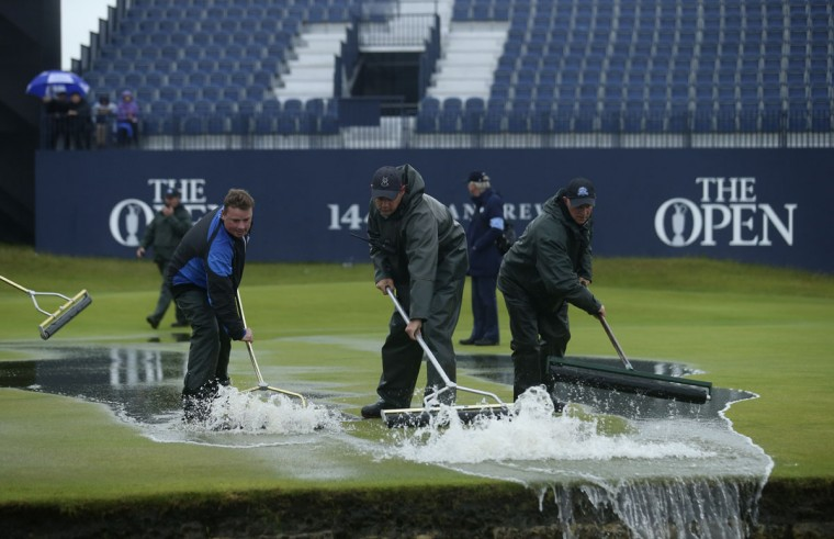 Groundskeepers use rollers to clear excess water after play was delayed by rain during the second round of the British Open Golf Championship at the Old Course, St. Andrews, Scotland, Friday, July 17, 2015. (AP Photo/Peter Morrison)