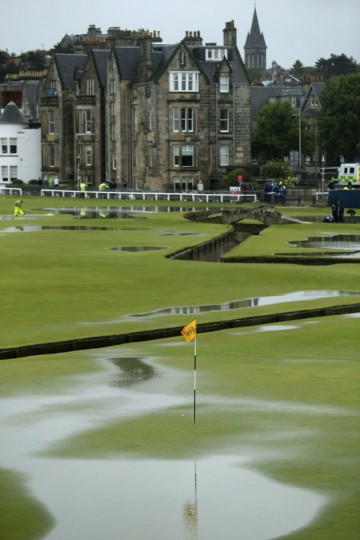 Rain water gathers on the first green after play was suspended due to rain during the second round of the British Open Golf Championship at the Old Course, St. Andrews, Scotland, Friday, July 17, 2015. (AP Photo/Peter Morrison)