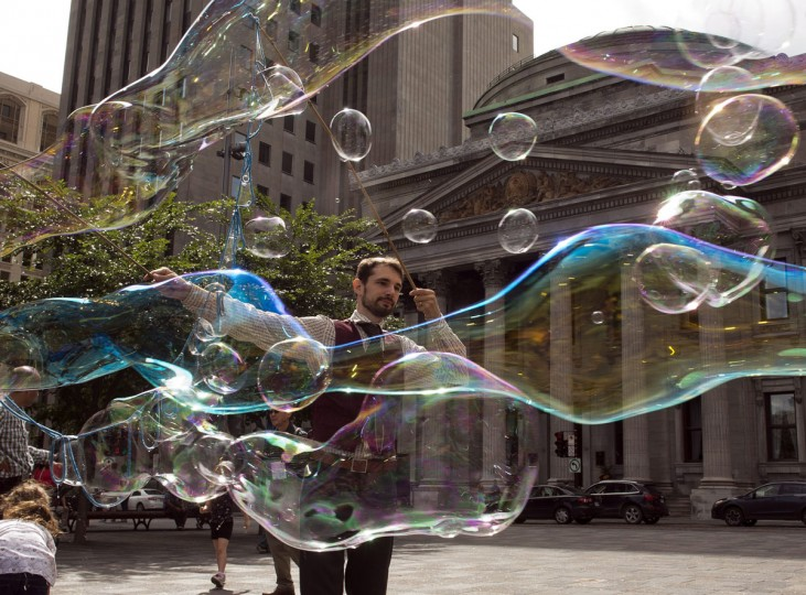"Robert, who is known as ""The Bubble Wizard"", entertains kids with bubbles in Old Montreal, Friday, July 24, 2015, in Montreal. (Ryan Remiorz/The Canadian Press via AP)"