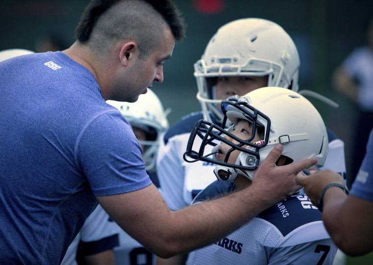 Coach Wes de Kirby, left, gives last-minute instructions to player Liu Jiayou, 9, right, just before the start of their American football game in Beijing. Chinaís capital might seem like an unlikely place to find American football, but interest among Chinese youth is growing. (AP Photo/Mark Schiefelbein)