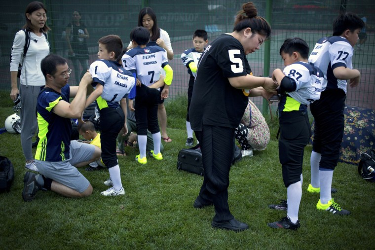 Chinese parents help their children put on sports jerseys and equipment before the start of their American football game in Beijing. Chinaís capital might seem like an unlikely place to find American football, but interest among Chinese youth is growing. (AP Photo/Mark Schiefelbein)