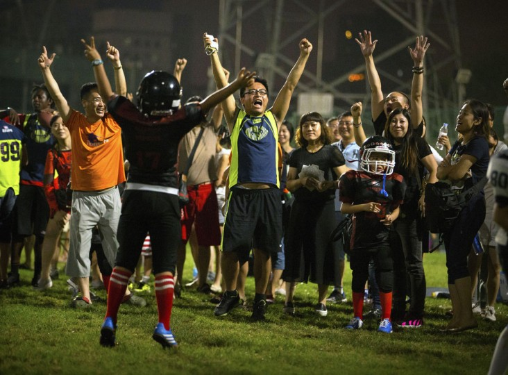 Parents and players from the Vipers team cheer after they scored a touchdown during their American football game in Beijing. Chinaís capital might seem like an unlikely place to find American football, but interest among Chinese youth is growing. (AP Photo/Mark Schiefelbein)