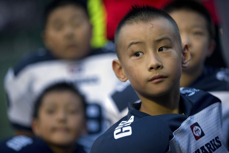 Guo Zhongyang, 7, listens to his coaches as they give a post-game pep talk after their American football game in Beijing. Chinaís capital might seem like an unlikely place to find American football, but interest among Chinese youth is growing. (AP Photo/Mark Schiefelbein)