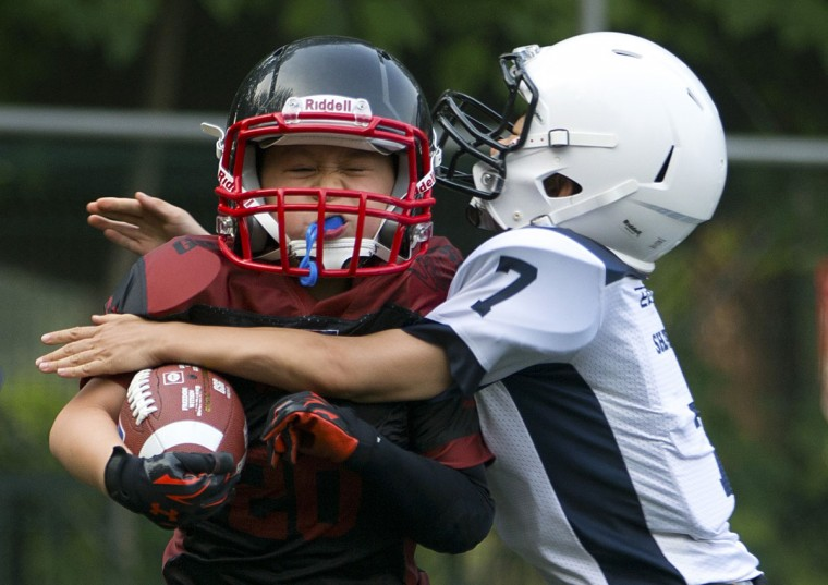 Ma Shichi, 9, of the Vipers, left, is tackled by Liu Jiayou, 9, of the Sharks, right, during their American football game in Beijing. Chinaís capital might seem like an unlikely place to find American football, but interest among Chinese youth is growing. (AP Photo/Mark Schiefelbein)