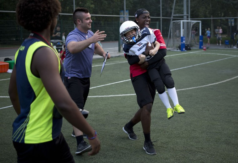 Guo Zhongyang, 7, is carried off the field by coach Ndizeye Amatus, right, while fellow coach Wes de Kirby, second from left, watches during their American football game in Beijing. Chinaís capital might seem like an unlikely place to find American football, but interest among Chinese youth is growing. (AP Photo/Mark Schiefelbein)
