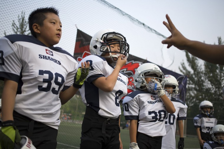 Jia Ziqi, 10, left, Lu Xiaoyu, 8, center, and Zhao Yuxiang, 8, right, listen to instructions from their coach during their American football game in Beijing. Chinaís capital might seem like an unlikely place to find American football, but interest among Chinese youth is growing. (AP Photo/Mark Schiefelbein)