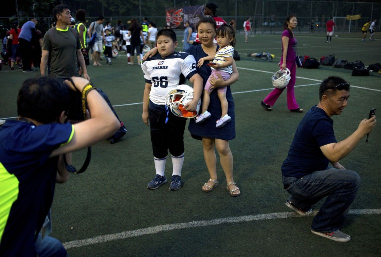 Zhang Yonghao, 8, poses for photos with family members after his American football game in Beijing. Chinaís capital might seem like an unlikely place to find American football, but interest among Chinese youth is growing. (AP Photo/Mark Schiefelbein)
