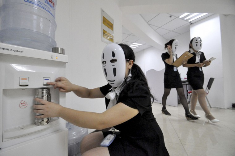 "Staff wearing masks during a work day at a property service company specializing in leased office space in Handan in northern China's Hebei province Tuesday, July 14, 2015. The company holds a monthly relaxation day at the office using various themes such as a ""faceless"" day when workers wear masks with the idea that they don't have to fake their facial expression through the day. (Chinatopix Via AP)"