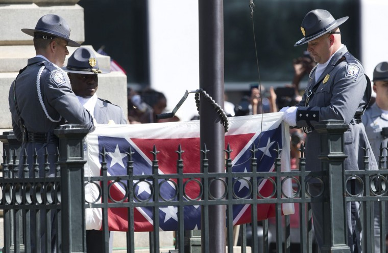 An honor guard from the South Carolina Highway patrol removes the Confederate battle flag from the Capitol grounds in Columbia, S.C., Friday, July 10, 2015, ending its 54-year presence there. (AP Photo/John Bazemore)