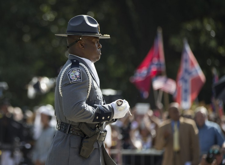 A member of an honor guard from the South Carolina Highway patrol carries a Confederate battle flag as they remove it from the Capitol grounds Friday, July 10, 2015, in Columbia, S.C. The Confederate flag was lowered from the grounds of the South Carolina Statehouse to the cheers of thousands on Friday, ending its 54-year presence there and marking a stunning political reversal in a state where many thought the rebel banner would fly indefinitely. (AP Photo/John Bazemore)