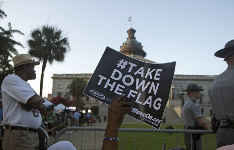 A woman waves a sign as she waits for the Confederate battle flag to be removed from in front of the South Carolina Statehouse, Friday, July 10, 2015, in Columbia, S.C. South Carolina Gov. Nikki Haley signed a bill into law Thursday requiring the flag to be removed. (AP Photo/John Bazemore)