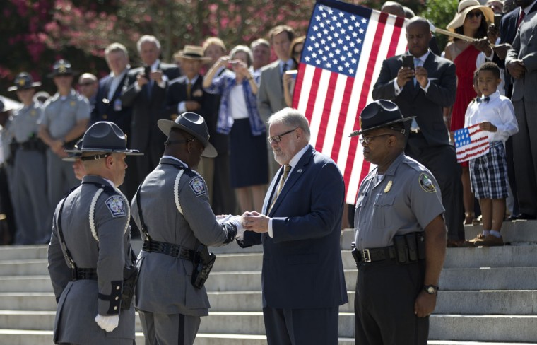 An honor guard member from the South Carolina Highway Patrol hands the Confederate battle flag that flew in front of the Statehouse to the curator of the Confederate Relic Room and Military Museum after it was taken down Friday, July 10, 2015, in Columbia, S.C. (AP Photo/John Bazemore)