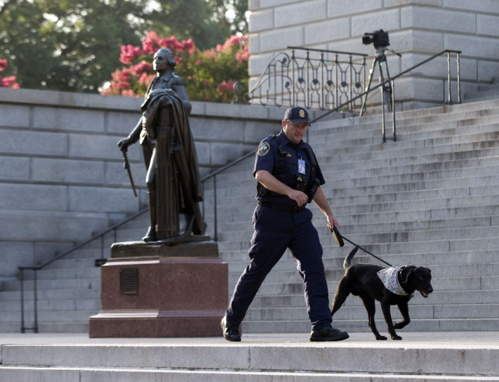 A police officer walks a dog on the steps of the South Carolina Statehouse as the state prepares to remove a Confederate battle flag from in front of the South Carolina Statehouse, Friday, July 10, 2015, in Columbia, S.C. South Carolina Gov. Nikki Haley signed a bill into law Thursday requiring the flag to be removed. (AP Photo/John Bazemore)