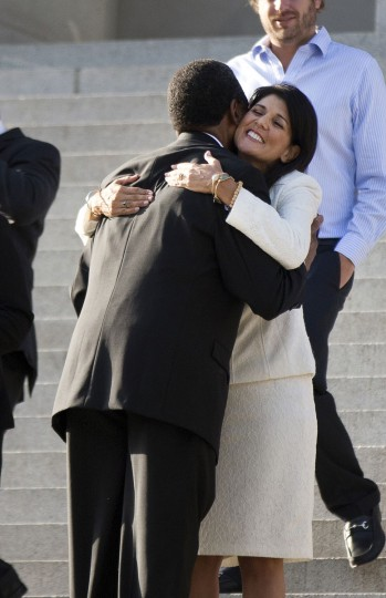 South Carolina Gov. Nikki Haley hugs Rev. Norvel Goff, interim pastor at Emanuel AME Church in Charleston, before an honor guard from the South Carolina Highway Patrol removed the Confederate battle flag from the Capitol grounds, Friday, July 10, 2015, in Columbia, S.C. (AP Photo/John Bazemore)