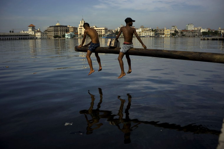 Youth cover a pole with oil as they prepare it for a competition over Havana Bay during a small fair in the Casablanca neighborhood of Havana, Cuba, Thursday, July 16, 2015. Casablanca residents have brought back lost traditions to their 420-year-old neighborhood, including this game in which contestants try to walk to the end of a wooden pole without slipping off into the water. A money prize is placed at the end of the pole for the winner. (AP Photo/Ramon Espinosa)