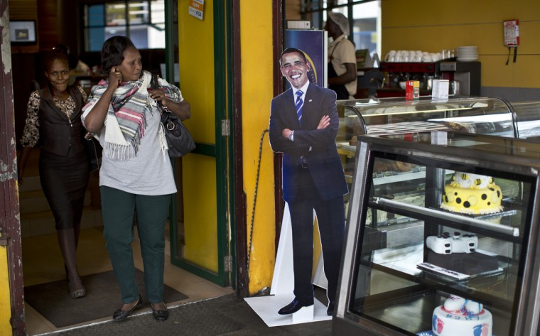 Customers walk past a cardboard cutout of President Barack Obama in the entranceway of the Cafe Deli coffee shop in downtown Nairobi, Kenya Wednesday, July 22, 2015. In his first trip to Kenya since he was a U.S. senator in 2006, Obama is scheduled to arrive in Kenya on Friday, the first stop on his two-nation African tour in which he will also visit Ethiopia. (AP Photo/Ben Curtis)