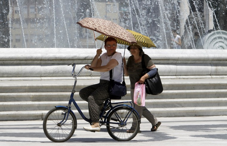 Women hold umbrellas to protect themselves from the sun, passing by a fountain in Skopje, Macedonia, Tuesday, July 7, 2015. A heat wave with temperature exceeding 38 degrees Celsius (100,4 Fahrenheit) has swept over this Balkan country. (AP Photo/Boris Grdanoski)