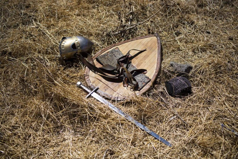 In this Saturday, July 4, 2015 photo, knight gear is laid on the ground after the reenactment of the Battle of Hattin in Horns of Hattin, northern Israel. Some 60 history buffs are re-enacting the famed battle near an extinct volcano in northern Israel overlooking the Sea of Galilee, where Saladin's army defeated the crusaders at the end of the 12th century. (AP Photo/Oded Balilty)