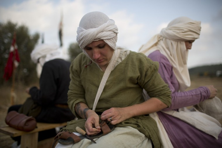 In this Thursday, July 2, 2015 photo, an Israeli member of a knight club fixes her sandal in the camp before marching 27 kilometers (17 miles) to the reenactment of the Battle of Hattin from the ancient northern city of Zippori to Horns of Hattin, northern Israel. Some 60 history buffs are re-enacting the famed battle near an extinct volcano in northern Israel overlooking the Sea of Galilee, where Saladin's army defeated the crusaders at the end of the 12th century. (AP Photo/Oded Balilty)