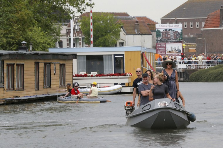 Spectators watch from little boats as the pack passes during the second stage of the Tour de France cycling race over 166 kilometers (103 miles) with start in Utrecht and finish in Neeltje Jans, Netherlands, Sunday, July 5, 2015. (AP Photo/Christophe Ena)