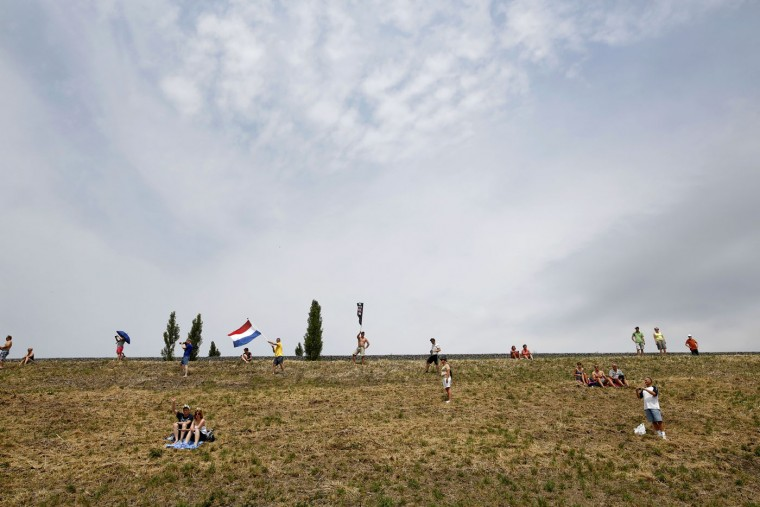 Spectators, one waving the Dutch flag, wait for the pack to pass during the second stage of the Tour de France cycling race over 166 kilometers (103 miles) with start in Utrecht and finish in Neeltje Jans, Netherlands, Sunday, July 5, 2015. (AP Photo/Laurent Cipriani)