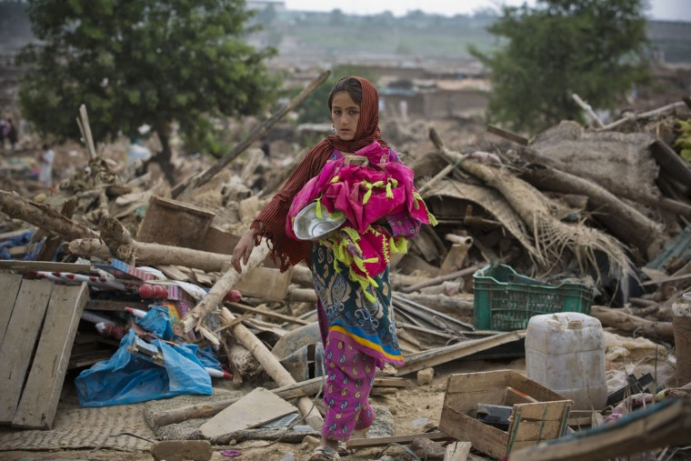 A girl collects her belongings from the debris of her house bulldozed by the government, in slums of Islamabad, Pakistan, Friday, July 31, 2015. Authorities demolished illegal mud houses of Afghan refugees and Pakistani tribal people who fled their villages due to ongoing crackdown operations against militants. Scores of people were injured during clashes between police and residents. (AP Photo/B.K. Bangash)